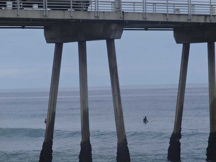 surfers-waiting-under-pier
