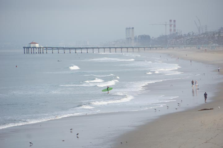 gray summer morning looking north to Manhattan Beach with surfers