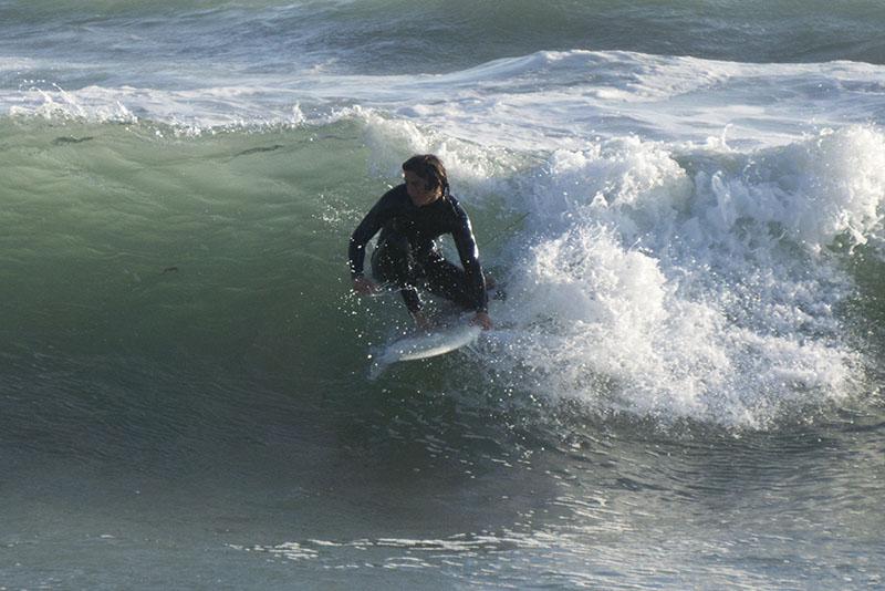 huntington-beach-surfer-grabbing-board-late-april