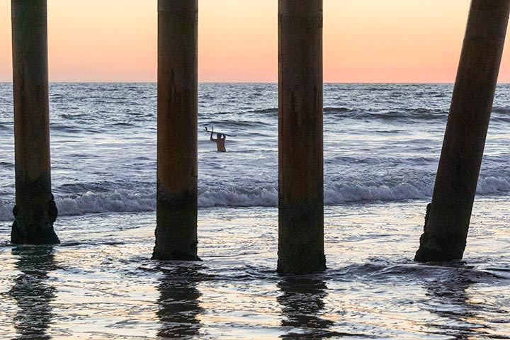 surfer-wading-out-twilight-through-pier-venice-beach